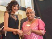 First Lady Margaret Kenyatta presents the female student of the year award to Ruhi Kamal Manek