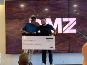 Raphael Mwachiti (far left) with Abdullah Snobar (far right), Executive Director of the DMZ, after winning the DMZ Sandbox competition.