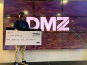 Raphael Mwachiti with his prize money after winning the DMZ Sandbox competition.