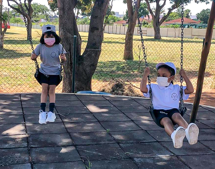 Early Years students playing on the swings