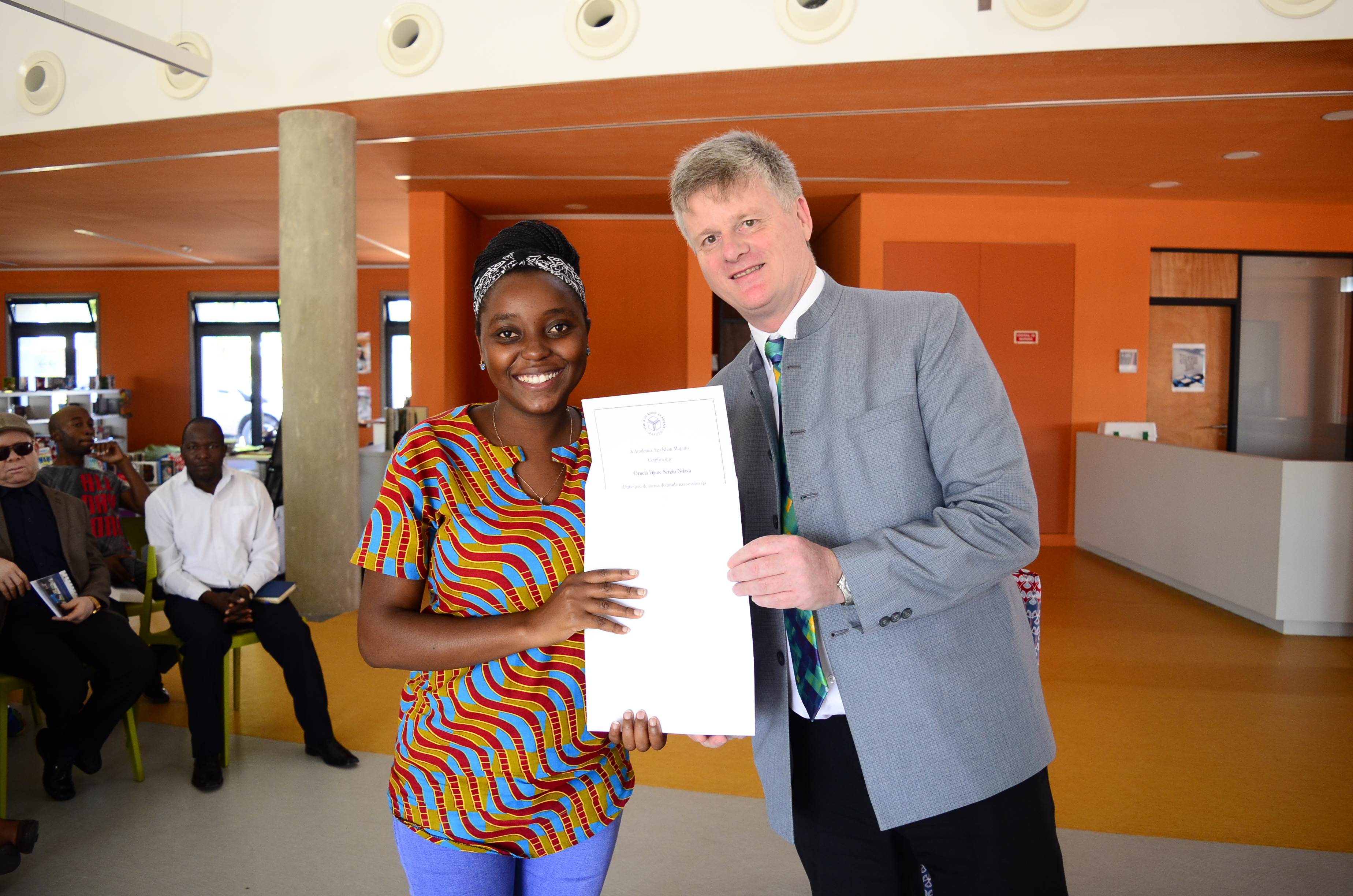 A teacher with her training completion certificate and the AKA Maputo Head of Academy