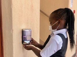 Student sanitising before entering a classroom